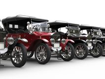 Vintage cars in a row - red stands out. Isolated on white background Royalty Free Stock Image