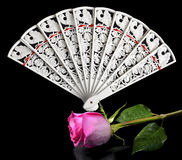 Vintage carved Ladies fan and pink rose. On a black background - a piquant accessory festive carnival costume royalty free stock images