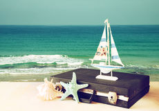Vintage case with old boat toy and starfish in front of seascape. travel concept. filtered image. Royalty Free Stock Photos