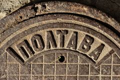 Vintage cast-iron sewer manhole USSR made with the inscription POLTAVA in the city of Dnipro, Ukraine, November 2018 fragment. Theft of manhole covers has royalty free stock image