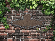 Vintage cast metal plate and climbing plant on the old brick wal Royalty Free Stock Photos