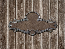Vintage cast metal plate on old wooden texture close-up Stock Photo