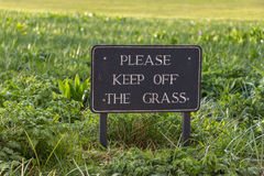 Vintage Caution Sign: Please Keep Off the Grass. On grass field background Royalty Free Stock Photo