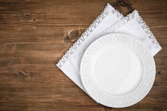 Vintage ceramic plate over table napkin on dark wooden background stock photography