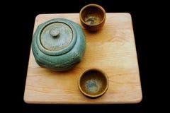 Vintage ceramic tea set on wood serving board isolated against black background. Basic ceramic tea service on wooden serving board. Copy space to right. Tea pot Royalty Free Stock Photo