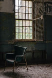 Vintage Chair - Abandoned Hospital / Sanitarium - New York. An interior view of a chair next to a window inside an abandoned hospital in New York stock photo