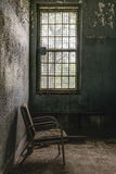 Vintage Chair - Abandoned Hospital / Sanitarium - New York. An interior view of a chair next to a window inside an abandoned hospital in New York stock images