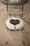 Vintage Chair with Bride written on love shaped sign. Vintage white chair with Bride written on love shaped sign hanging on back of chair Royalty Free Stock Photos