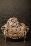 Vintage chair with gold accents beside the wall Royalty Free Stock Photography