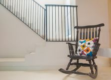 Vintage Chair in the modern room. Vintage Chair in the modern room with colourful pillow on the chair and stairway background Royalty Free Stock Image