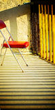 Vintage Chair - Modernist Furniture. Interior retro design chair - vinyl and chrome on balcony (patio) with sunset shadow lines Royalty Free Stock Photo