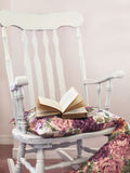 Vintage chair with pillows and book Stock Image