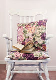 Vintage chair with pillows and book Stock Photography