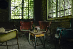 Vintage Chairs and Cigarettes - Abandoned Hospital / Sanitarium - New York. An interior view of a vintage chairs around a table with cigarettes inside an stock photography