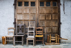 Vintage chairs lined up outside wooden doors of stone outbuildin Stock Photo