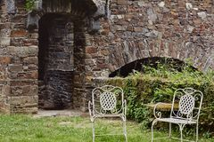 Vintage chairs outdoor in courtyard of medieval castle. Two vintage white chairs outdoor in green courtyard of medieval castle royalty free stock photography