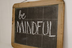 Vintage chalkboard with the motto Be Mindful. Old vintage chalkboard with a handwritten message, a motto or resolution Stock Photo