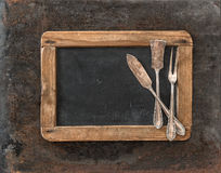 Vintage chalkboard and silver cutlery on rusted metal background Stock Photos