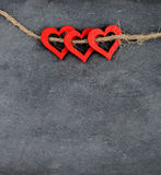 Vintage chalkboard with three red heart shape symbols on rope Royalty Free Stock Images