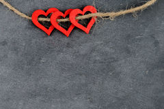 Vintage chalkboard with three red heart shape symbols on rope Stock Photos