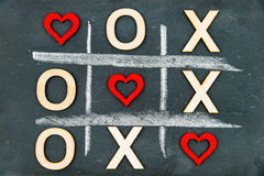 Vintage chalkboard with Tic Tac Toe Game. Competition XO Win created of wood letters and red hearts, letters O and X replaced with red heart shapes, Challenge royalty free stock images