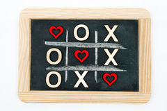 Vintage chalkboard with Tic Tac Toe Game. Competition XO Win created of wood letters and red hearts, letters O and X replaced with red heart shapes, isolated on royalty free stock photography