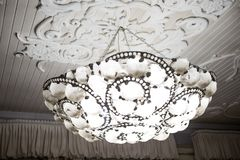 Vintage chandelier hanging under white ceiling with stucco moldings stock photography