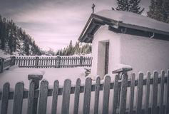 Vintage chapel in winter settings. Winter scenery with a small, rustic chapel covered with snow, surrounded by a wooden fence and snowy trees. Image captured in Stock Photos