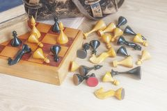 Vintage chess and an old leather bag on the wooden surface. stock photos