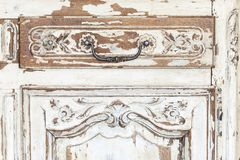 Vintage chest of drawers with carving white color with fading and metal handle. Close-up. Selective focus stock photos