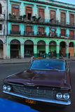 Vintage Chevrolet car of Cuba in front of old building in Havana. Dark purplish brown Vintage Chevrolet car of Cuba parked in front of old European Colonial Royalty Free Stock Photo