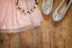 Vintage chiffon girl's dress, floral tiara next to ballet shoes on wooden background. vintage filtered image Stock Photo