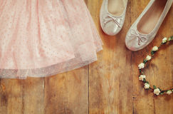 Vintage chiffon girl's dress, floral tiara next to ballet shoes on wooden background. vintage filtered image Stock Image