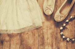 Vintage chiffon girl's dress, floral tiara next to ballet shoes on wooden background. vintage filtered, sepia style image Stock Photography