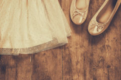Vintage chiffon girl's dress next to ballet shoes on wooden background. vintage filtered, sepia style image Royalty Free Stock Photo