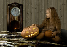 Vintage children. Halloween, cute little girl sitting next to a pumpkin glowing and looks at the clock Stock Photos