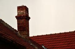 Vintage chimney on roof. Old brick chimney on red roof under sky vintage background Stock Image