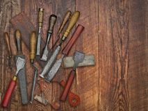 Vintage chisels and stones collage over old wooden bench Royalty Free Stock Photos