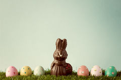 Vintage chocolate bunny with easter eggs over grass Royalty Free Stock Photography