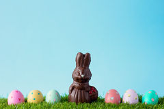 Vintage chocolate bunny with easter eggs over grass Royalty Free Stock Photo