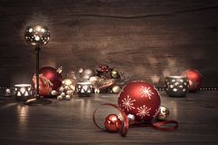 Vintage Christmas background with candles and Christmas baubles. This image is toned Stock Photo