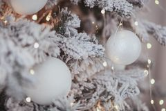 Vintage Christmas background with Christmas decoration on tree. White ball in focus and lights bokeh Royalty Free Stock Photography