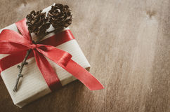 Vintage Christmas background. Kraft boxes with gifts, tied with red ribbons and pine cones in rustic style. Stock Photos