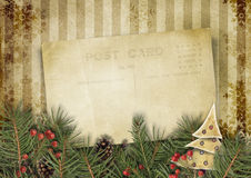 Vintage Christmas background with old postcard and firtree. Grungy Christmas background with fir branches and holly with space for photos and congratulations Stock Image