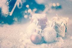 Vintage Christmas balls and gift boxes over snow background Stock Photo