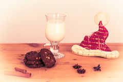 Vintage christmas dinner for santa. Wooden table with a glas of milk, some cookies and a santa hat Stock Photos