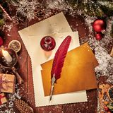 Vintage Christmas flat lay still life background with paper and red feather quill pen surrounded by pine foliage, decorations and stock photos