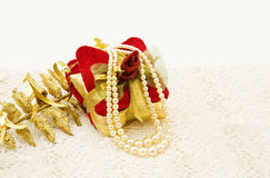 Vintage Christmas gift decoration. Vintage Christmas presents decoration and pearls on old handmade lace Royalty Free Stock Photos