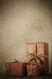 Vintage Christmas Gifts Arrangement. Vintage style image of gifts wrapped in paper and tied with gingham ribbon on a wood planked table with parchment background Royalty Free Stock Images