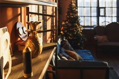 Vintage christmas interior with a bookcase, christmas tree, sofa, posters, photos and lettering in frames against the. Orange wall in the sunlight from big stock photos